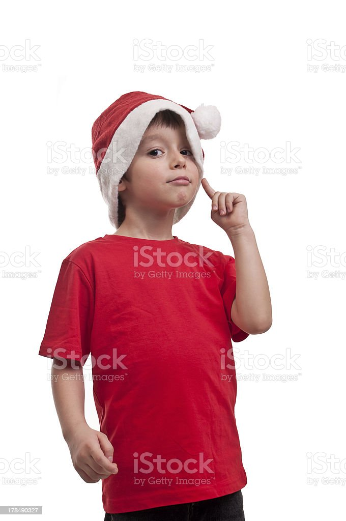 little boy in hat of Santa Claus with finger cheek royalty-free stock photo