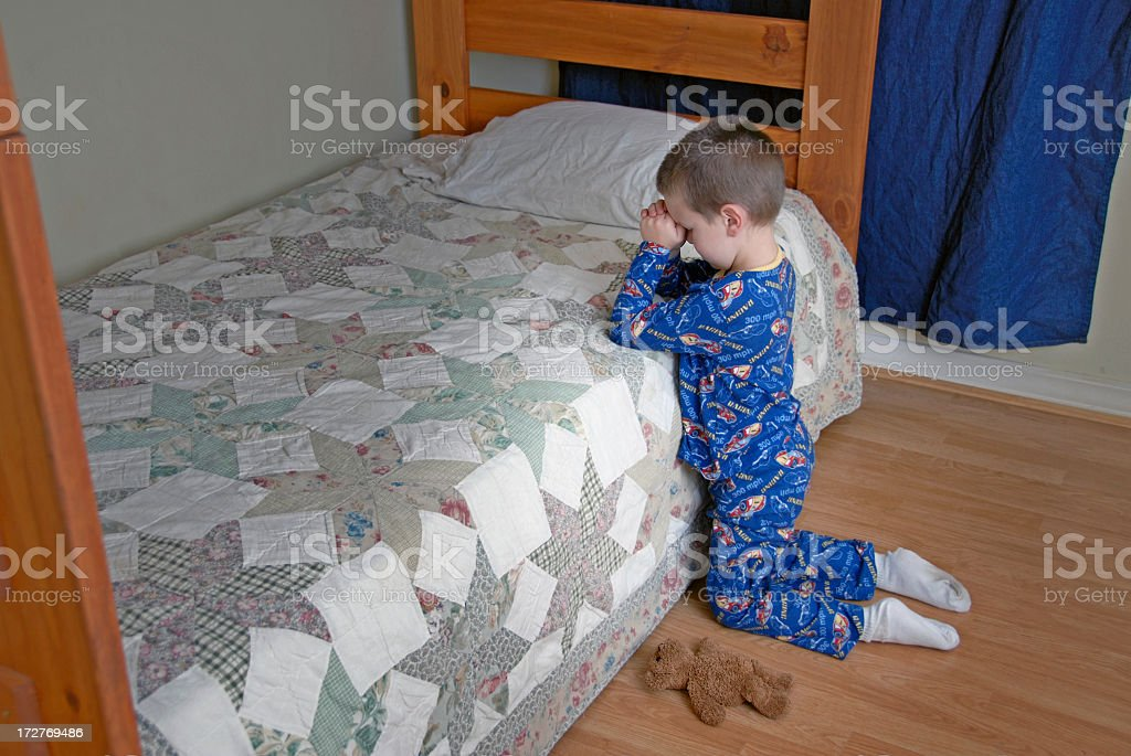A little boy in his room saying prayers stock photo