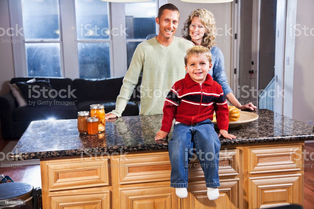 Little boy in kitchen with parents stock photo