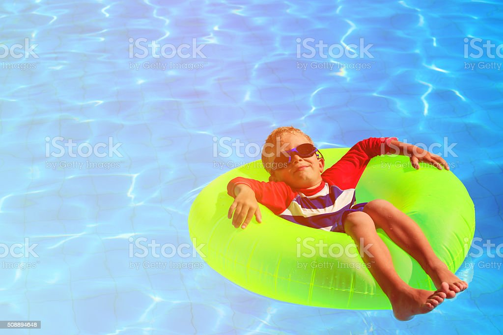 little boy in life ring having fun on beach stock photo