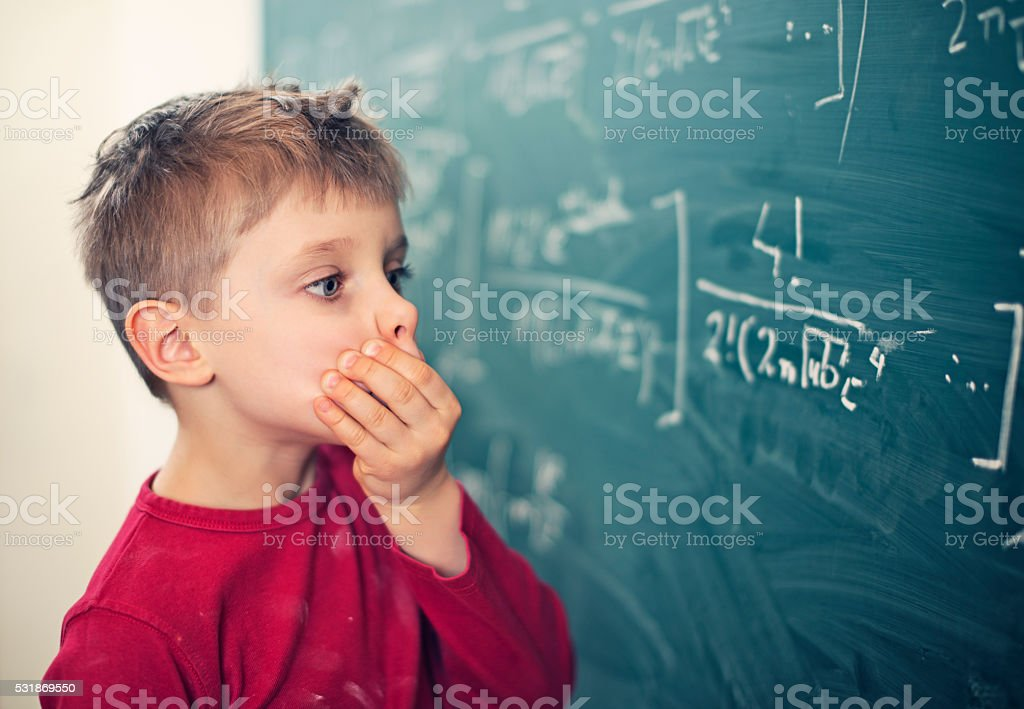 Little boy in math class overwhelmed by the math formula stock photo