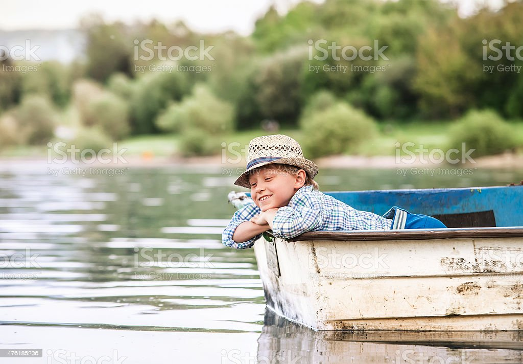 Little boy in old boat on the calm lake surface stock photo