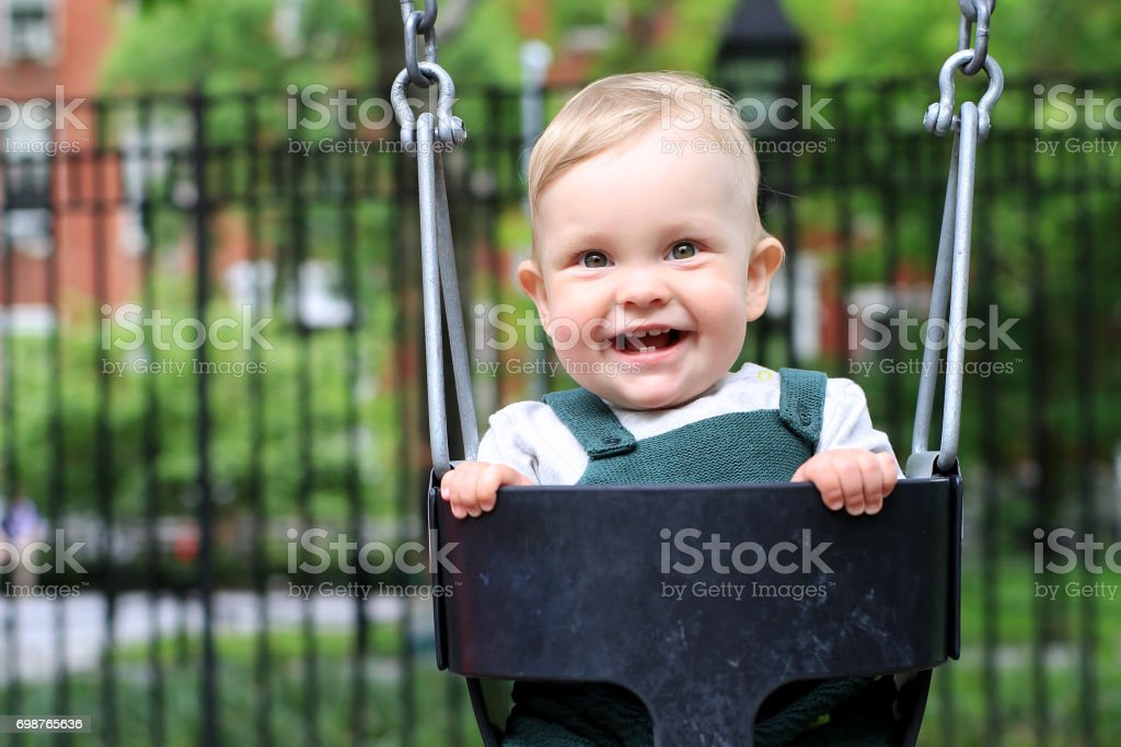 Little boy in overalls on the swing stock photo