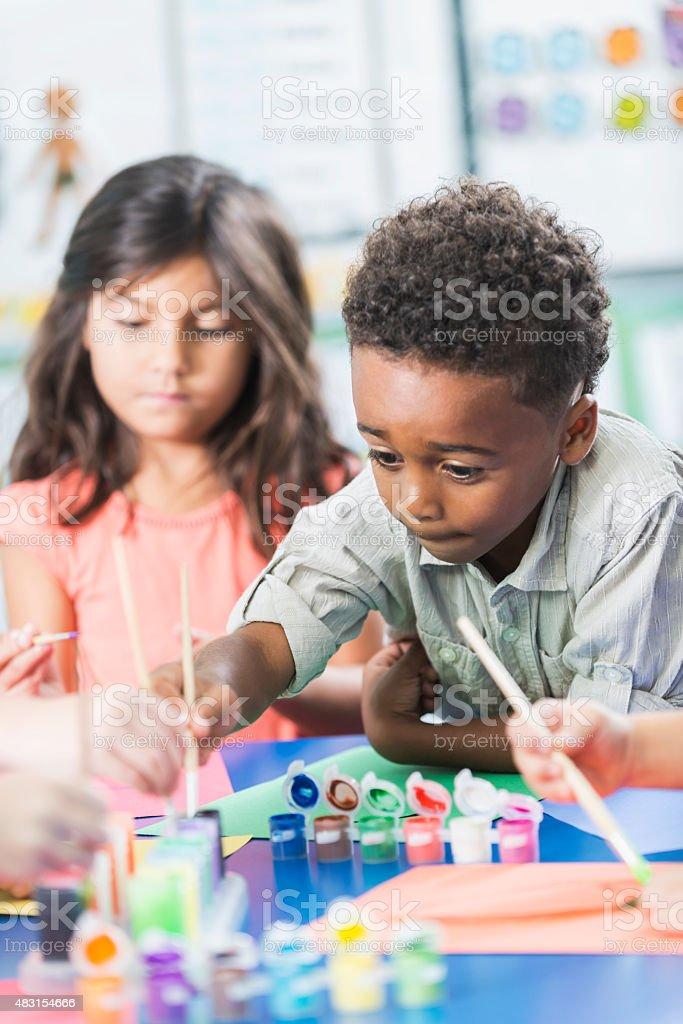 Little boy in preschool class doing art project stock photo