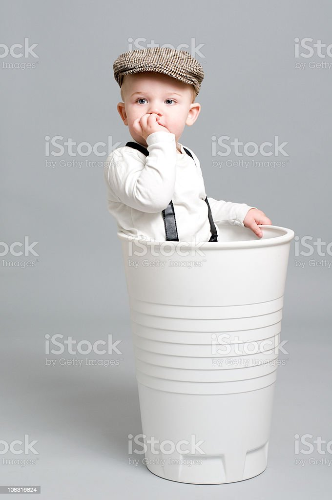 Little Boy in retro clothes stands in giant paper cup stock photo