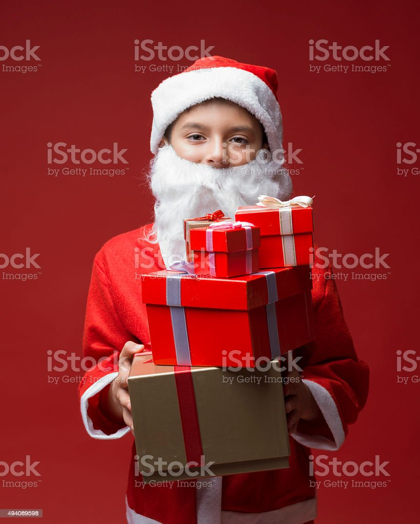 Little boy in santa costume giving gifts stock photo