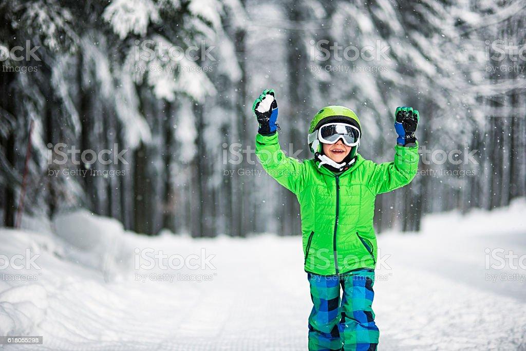 Little boy in ski outfit enjoying snow stock photo