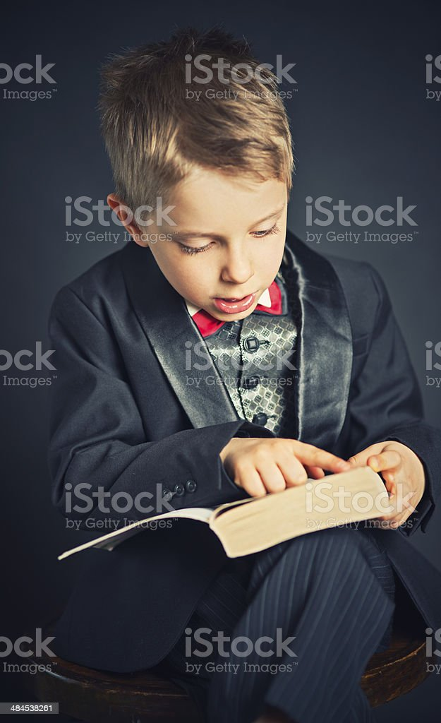 Little boy in suit reading book stock photo