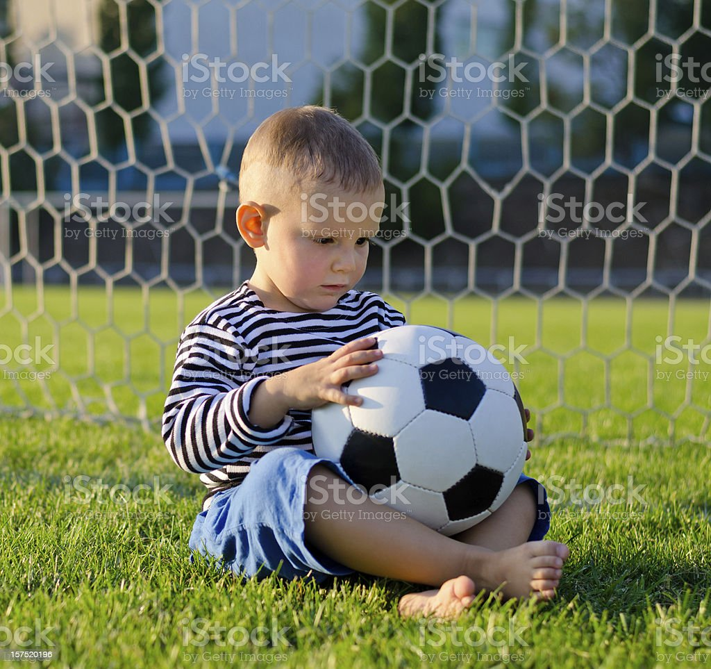 Little boy in the goal with his soccer ball stock photo