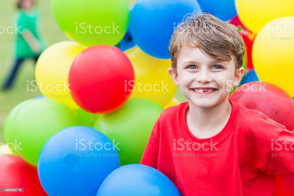 Little boy in the middle of big bunch of balloons stock photo
