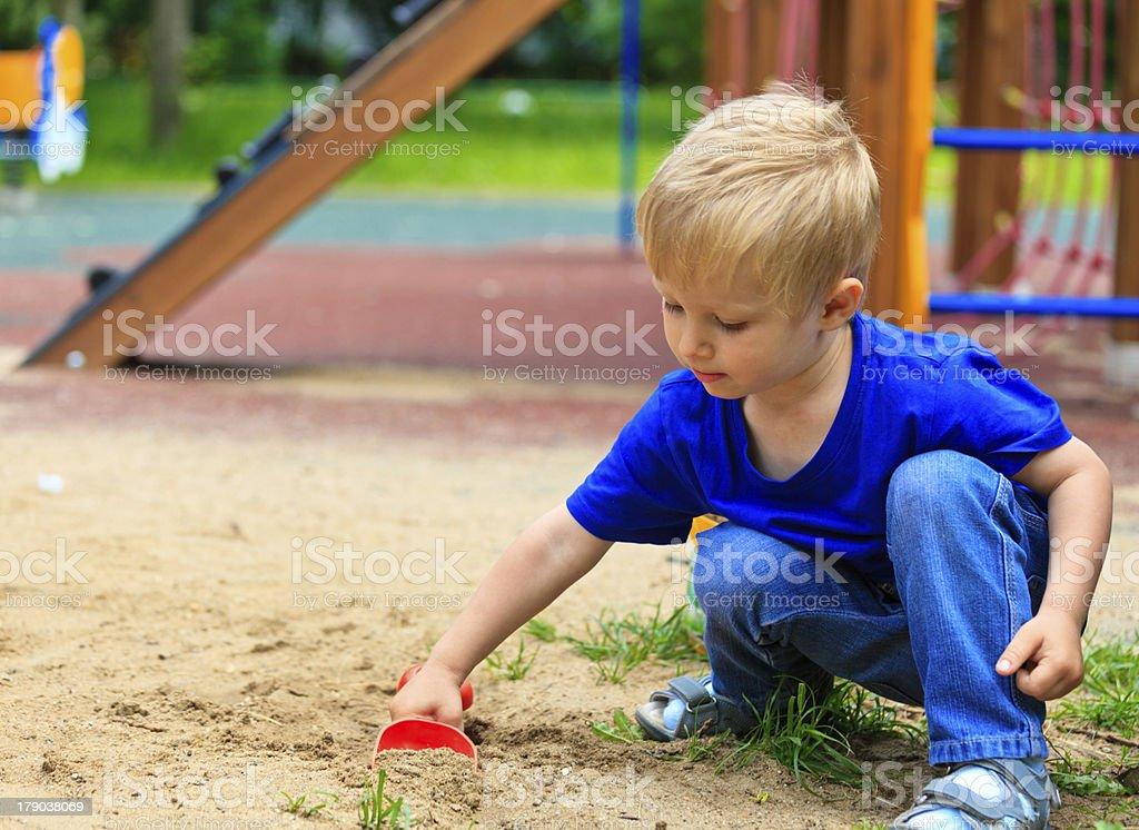 little boy in the sandbox stock photo