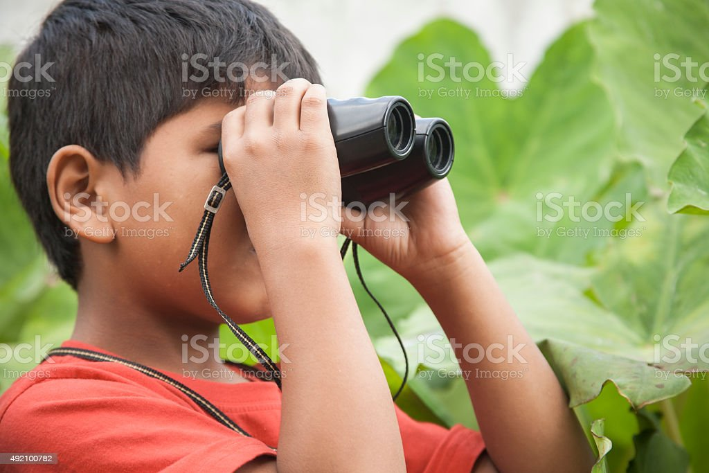 Little boy in tropical climate explores outdoors using binoculars. stock photo