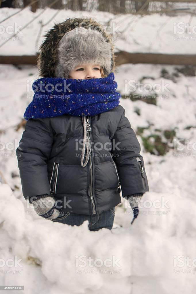 Little boy in warm clothing standing in a snow. stock photo