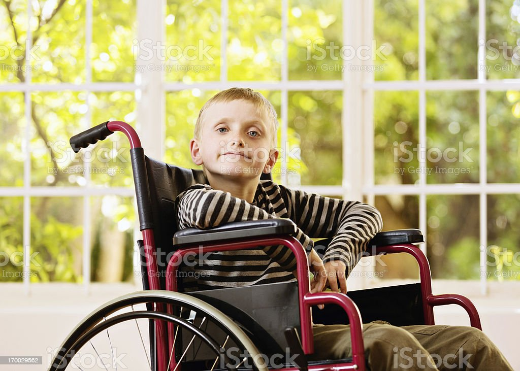 Little boy in wheelchair gives challenging look stock photo