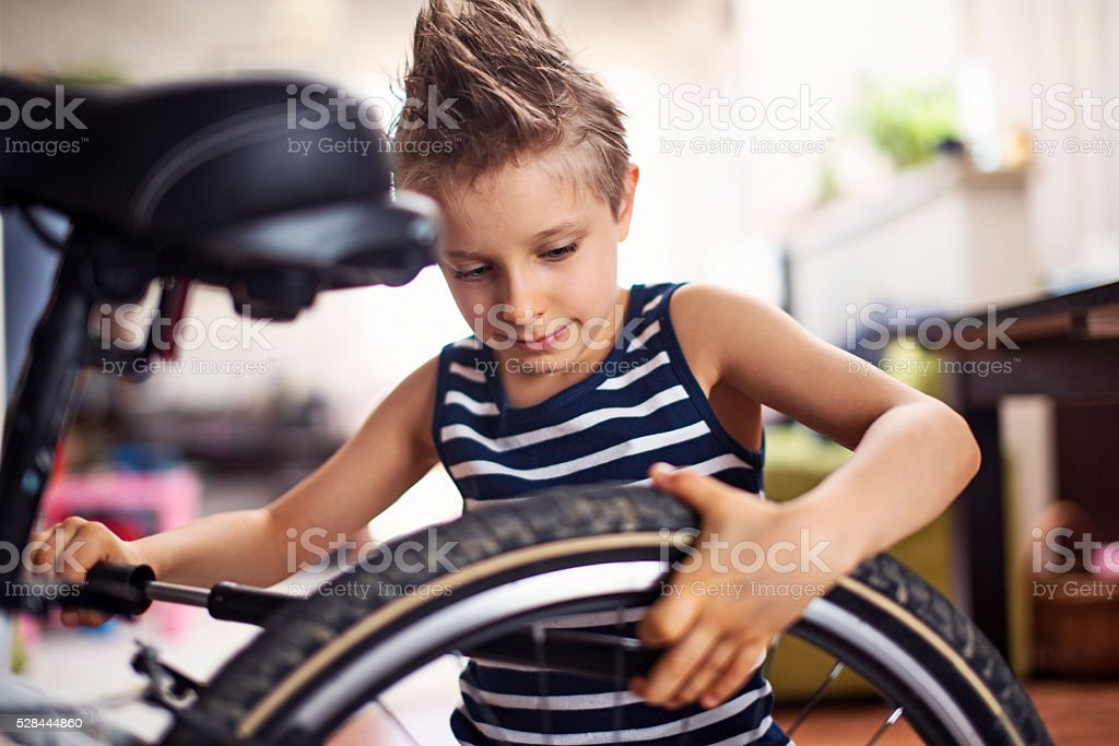 Little boy inflating a bicycle tyre stock photo