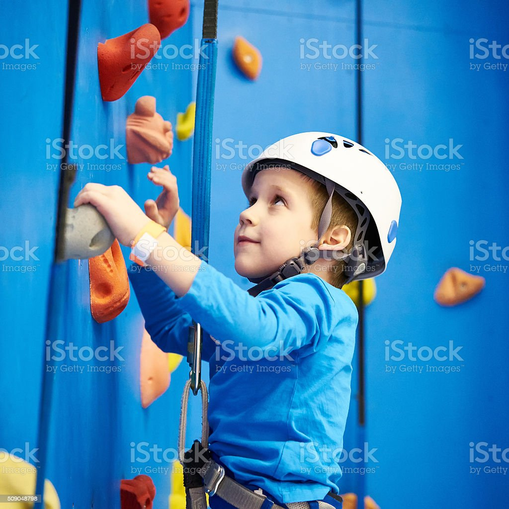 Little boy is climbing in sport park on blue wall stock photo