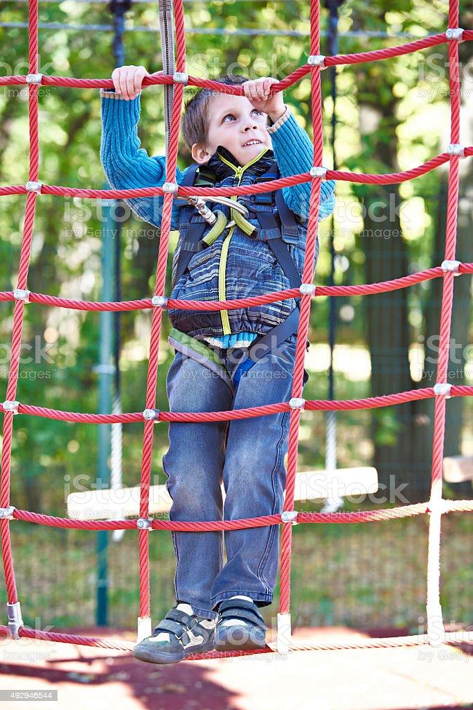 Little boy is climbing to amusement park stock photo