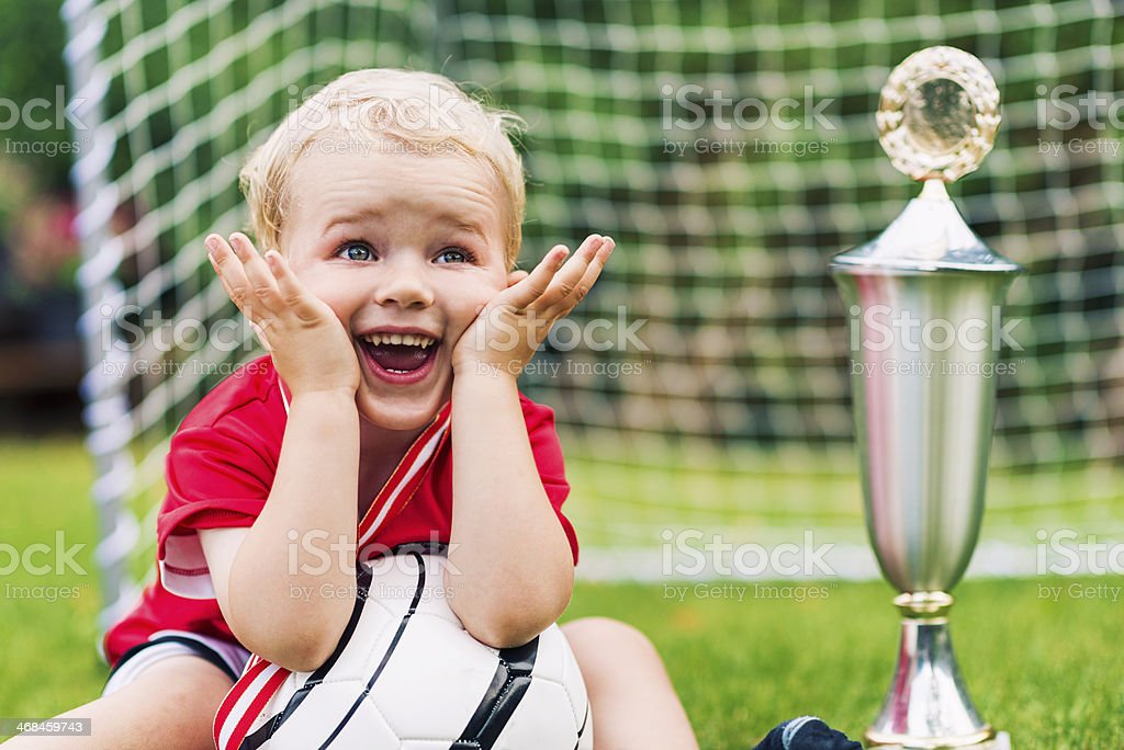 Little boy is really surprised after winning a trophy royalty-free stock photo