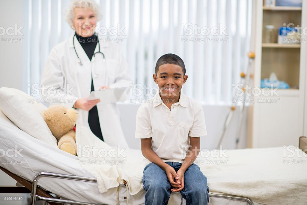 A little boy is sitting on a hospital bed next to stock photo