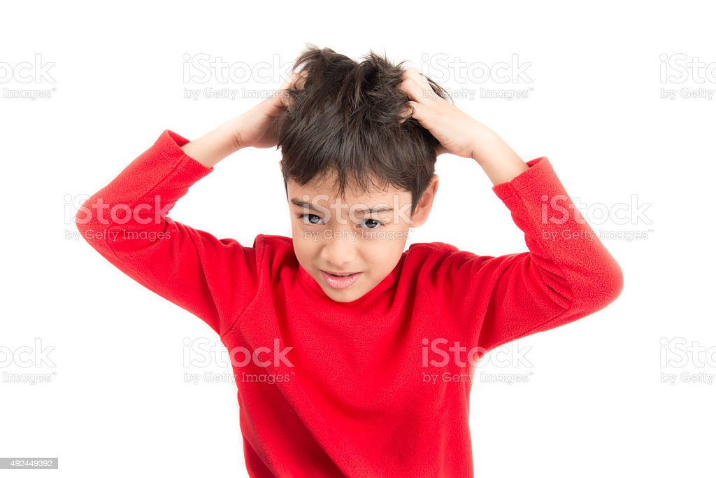 Little boy itchy his hair on white background stock photo