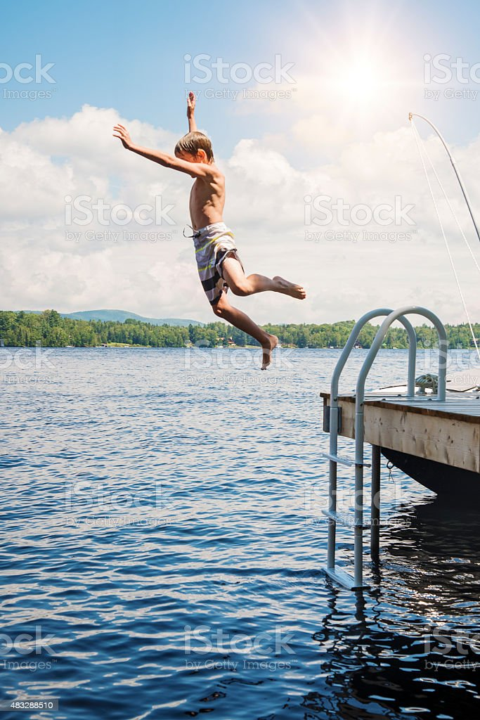 Little boy jumping in lake from pier on sunny day. stock photo