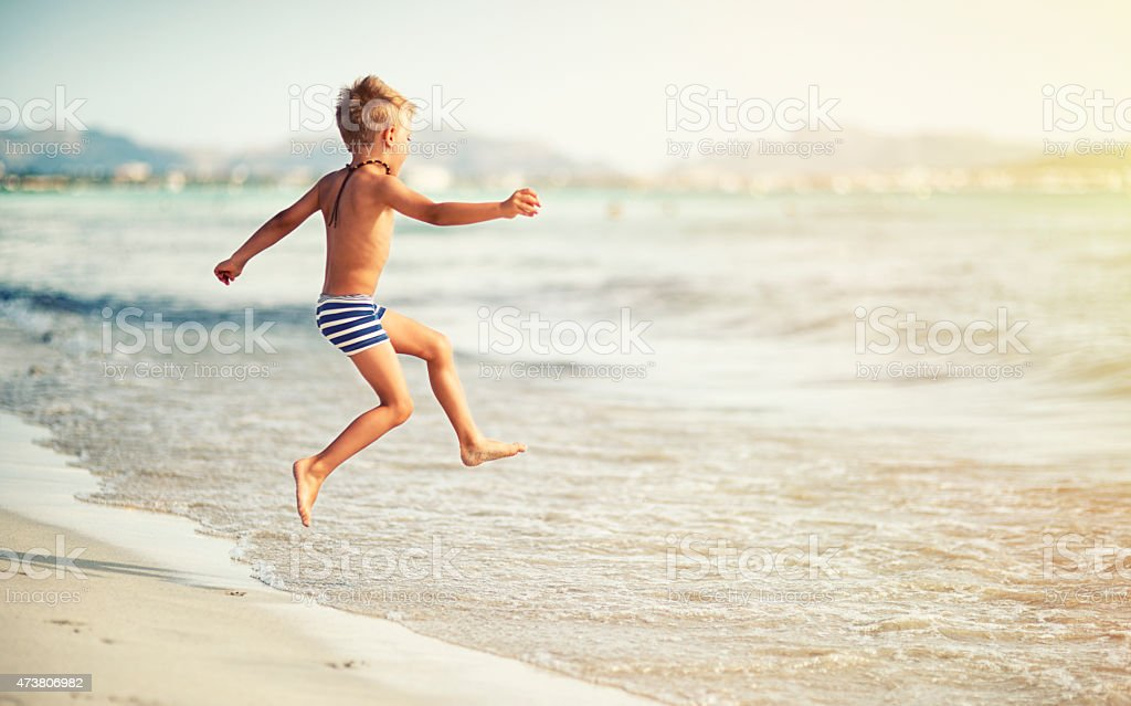 Little boy jumping into the sea stock photo