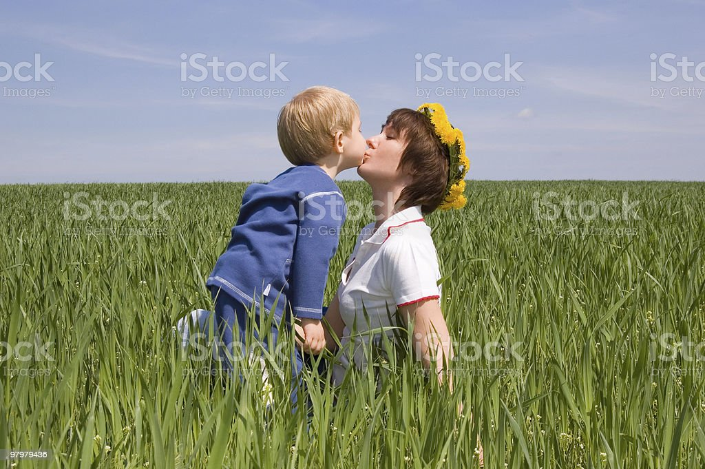 little boy kiss his mother on a field royalty-free stock photo