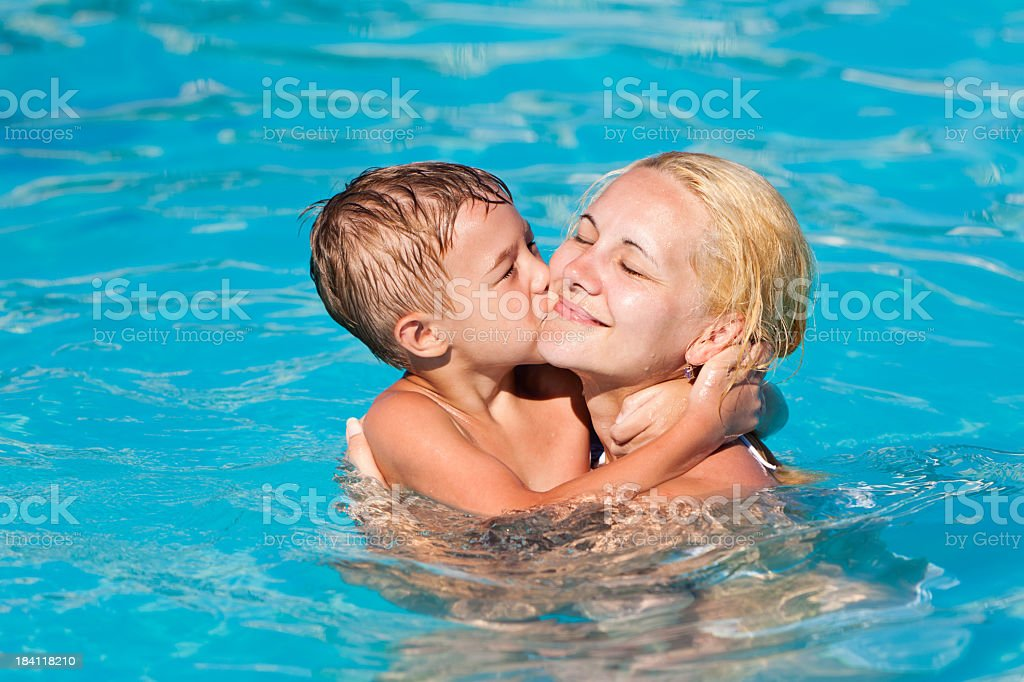 Little boy kissing his mother in the swimming pool royalty-free stock photo