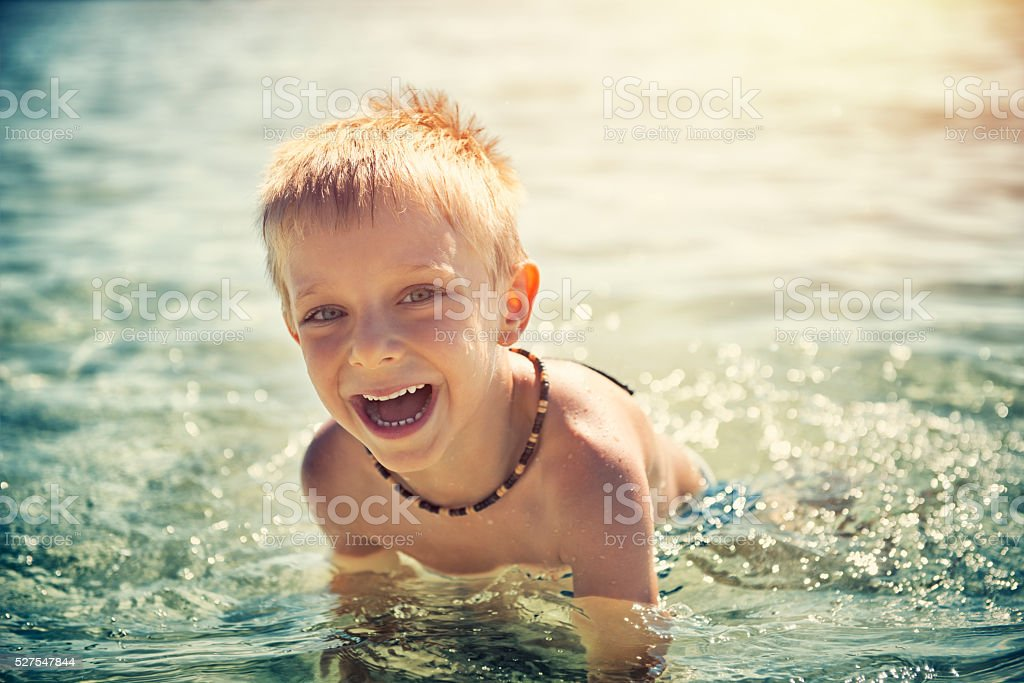 Little boy laughing and playing in sea stock photo