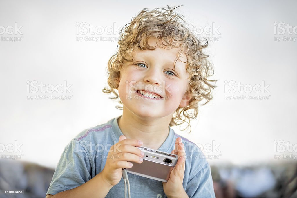 Little boy laughing and playing with a camera. royalty-free stock photo