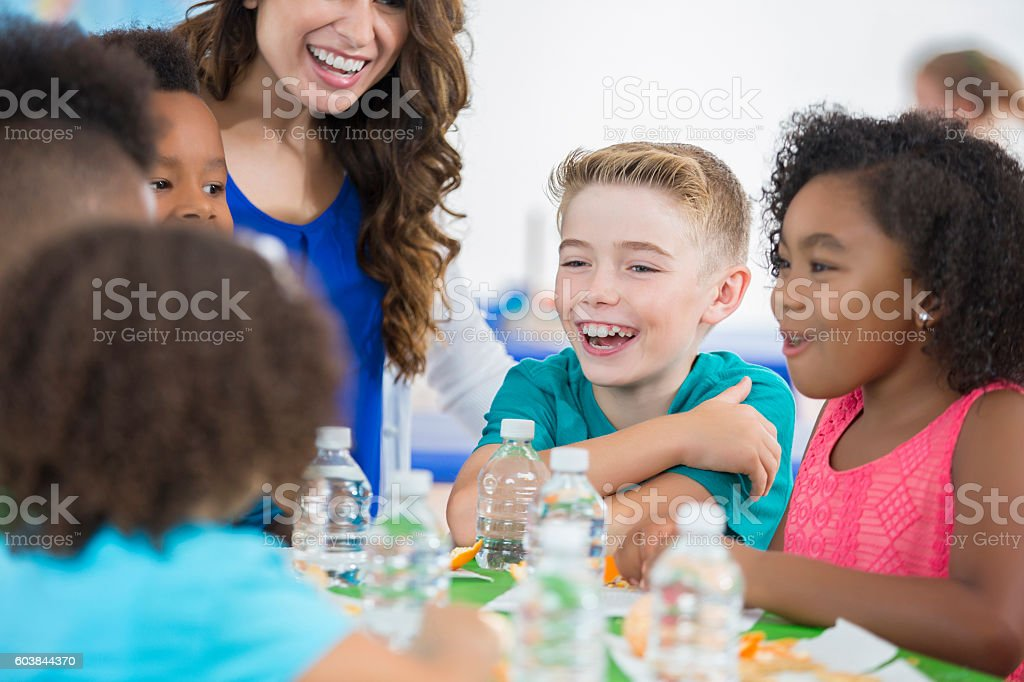 Little boy laughing with friends during daycare snack time stock photo