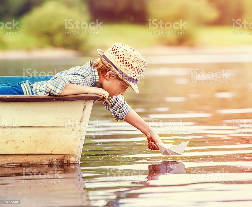 Little boy launch paper ship from old boat stock photo