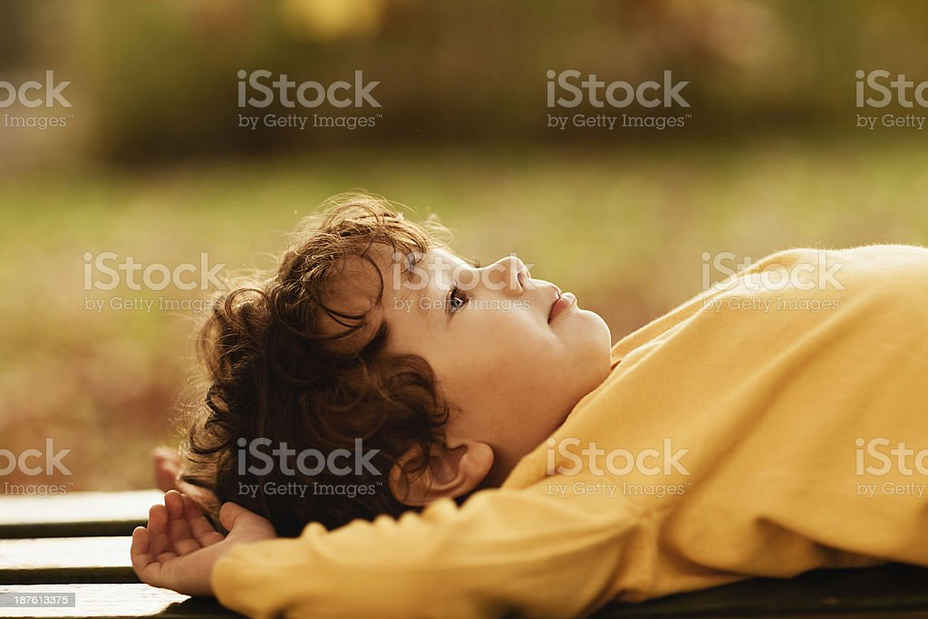 Little boy laying on bench royalty-free stock photo