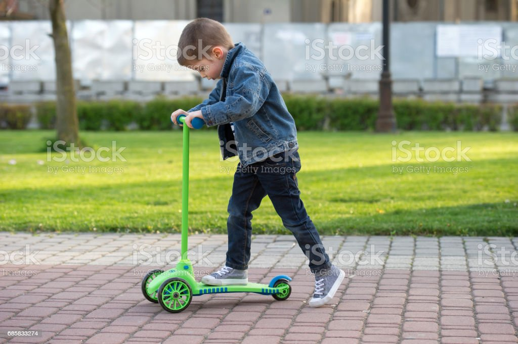 little boy learn to ride scooter in a park stock photo