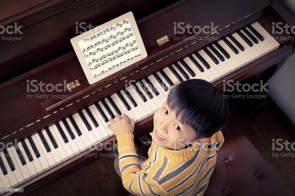 Little boy learning to play the piano royalty-free stock photo