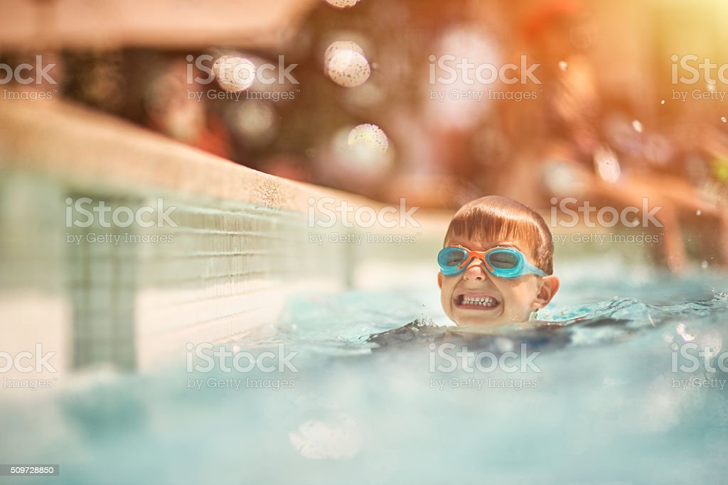 Little boy learning to swim in swimming pool stock photo