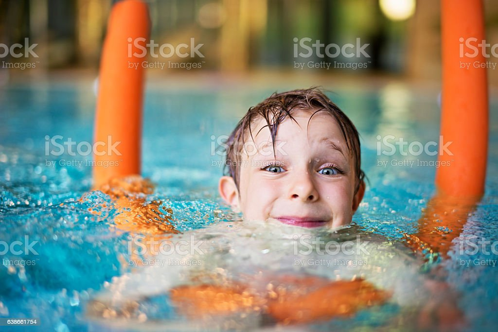 Little boy learning to swim with pool noodle stock photo