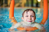 Little boy learning to swim with pool noodle