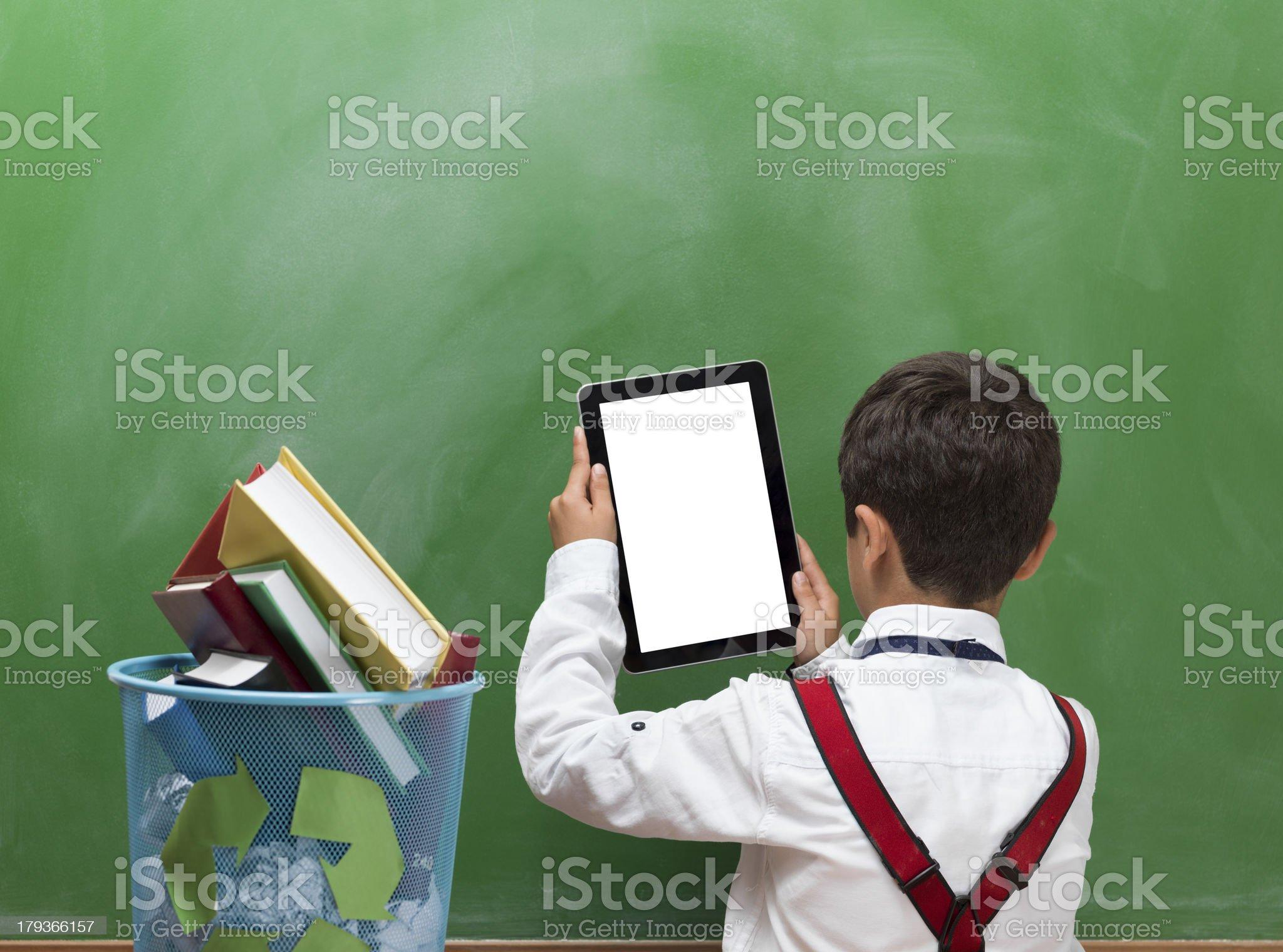 Little boy leaving books in recycling bin, using digital tablet royalty-free stock photo