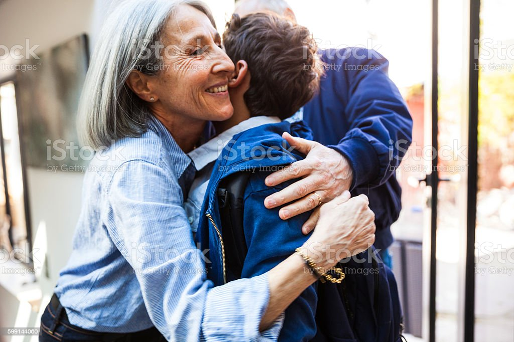 Little boy leaving for school with grandparents in the morning stock photo