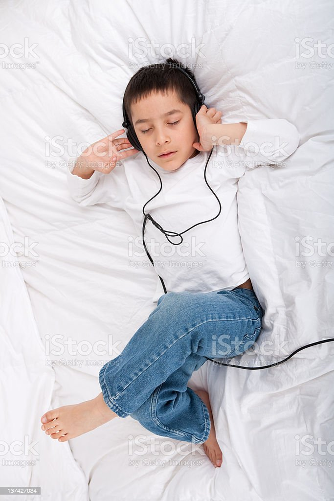 Little boy listening to headphones in bed royalty-free stock photo