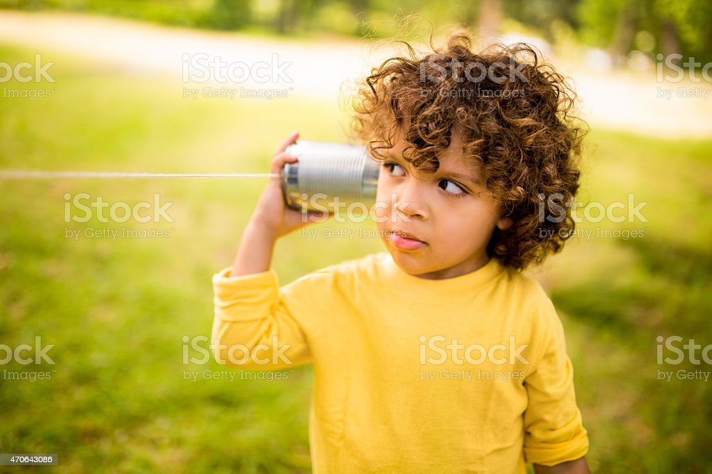 Little boy listening to sound through a tin can phone stock photo