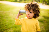 Little boy listening to sound through a tin can phone