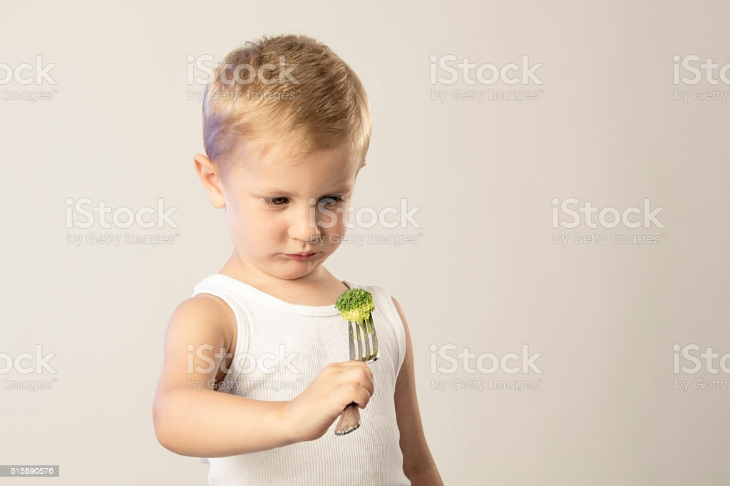 Little Boy Looking at Broccoli on His Fork stock photo