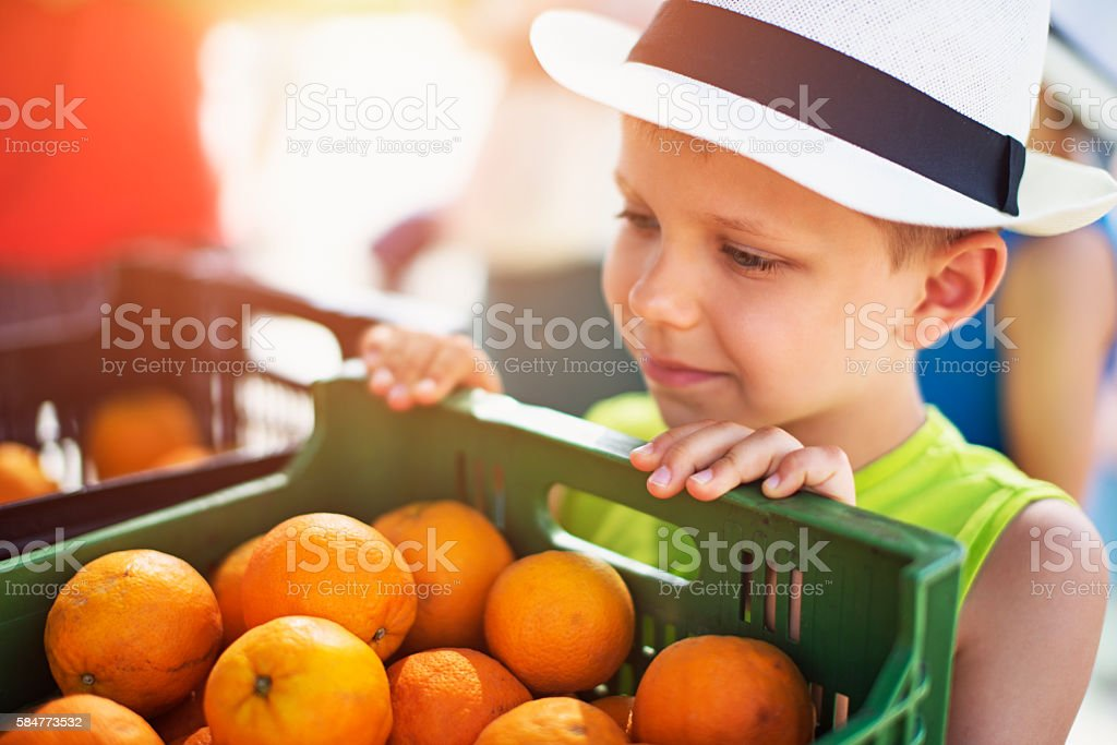 Little boy looking at oranges at the majorcan farmer's market stock photo