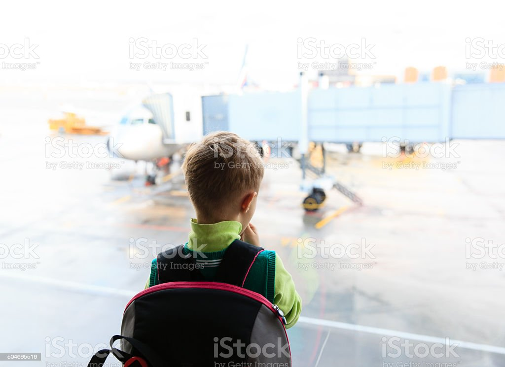 little boy looking at planes in the airport stock photo