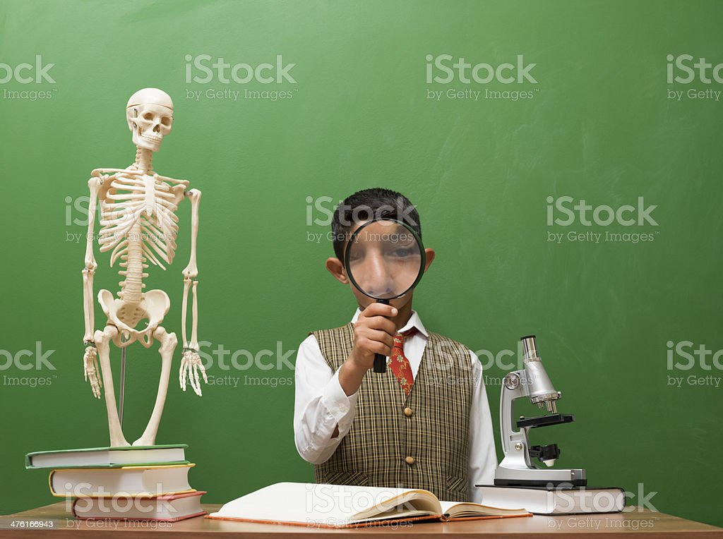 Little boy looking at the human skeleton and thinking royalty-free stock photo