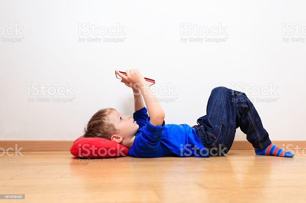 little boy looking at touch pad, early learning stock photo