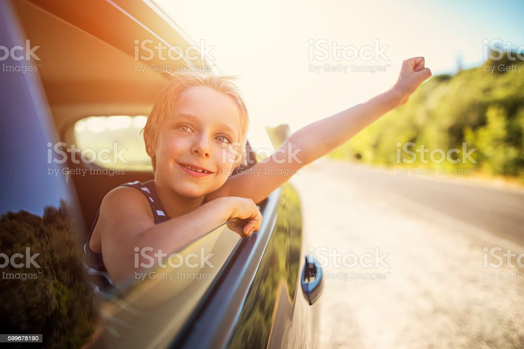 Little boy looking out of car on a road trip stock photo