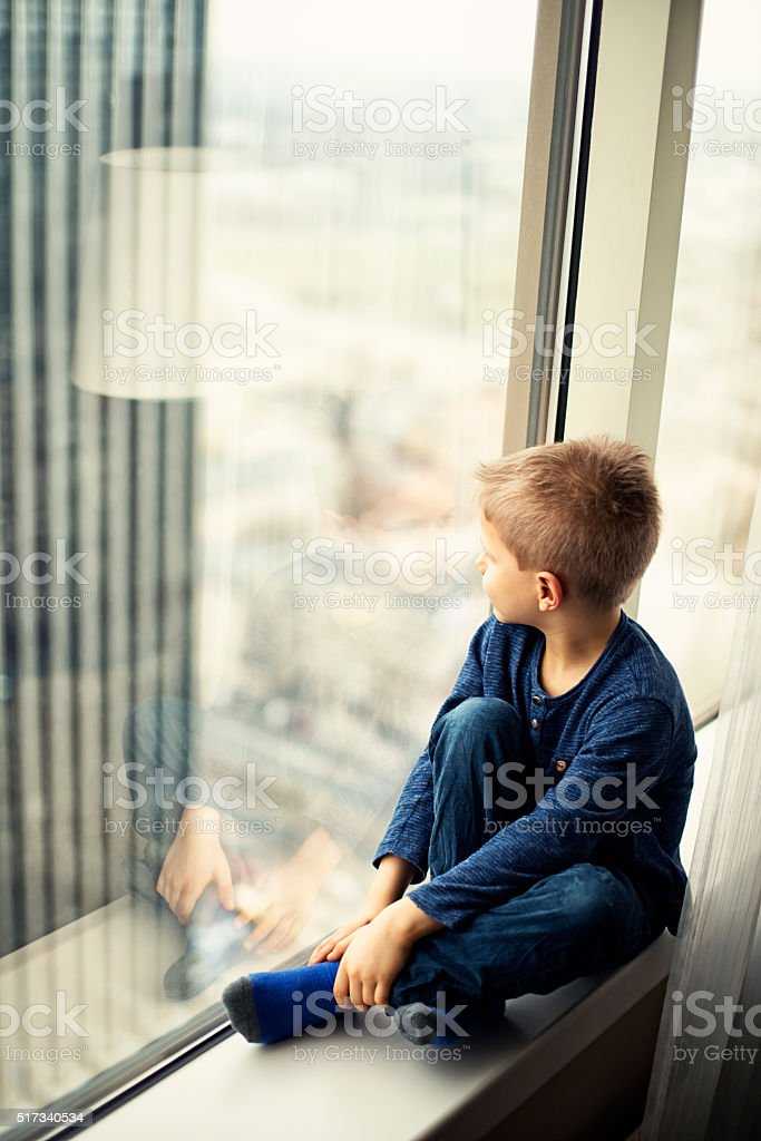 Little boy looking out of modern high rise appartment window stock photo